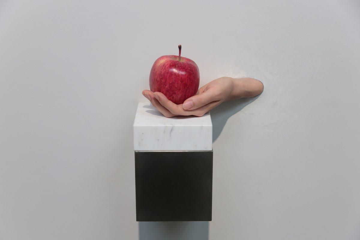 タイトル:りんごと手<br /> 素材: 生きた人間の左手、りんご(木材に油彩)大理石、ステンレス<br /> サイズ:実物大<br /> 制作年:2018<br /> 写真:Kenji Otani